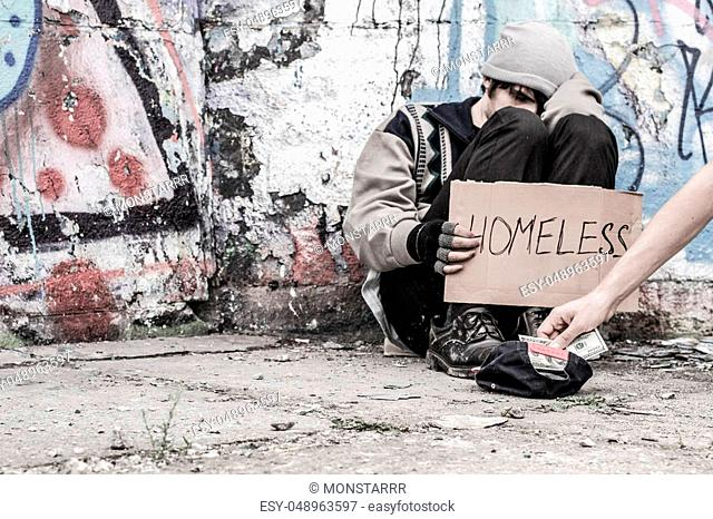 Homeless man being handed money by volunteer