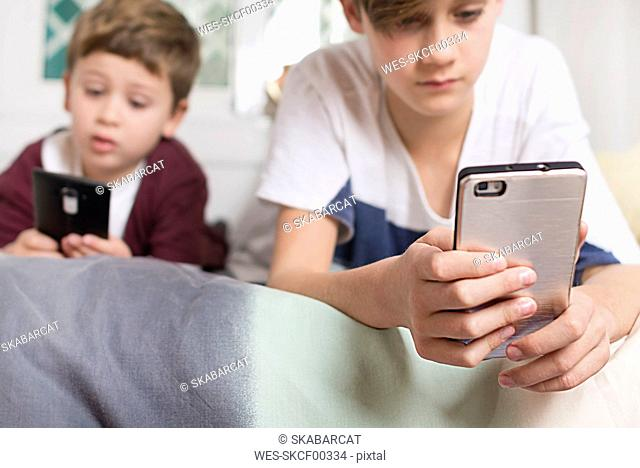 Two boys lying on bed at home using cell phones