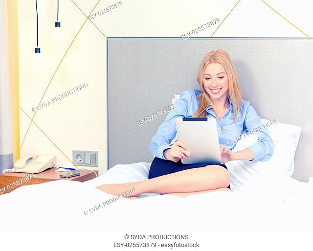 business, technology, internet and hotel concept - happy businesswoman with tablet pc computer lying in hotel in bed