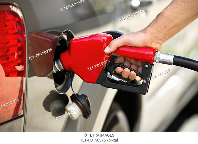 Hand holding fuel pump refueling car