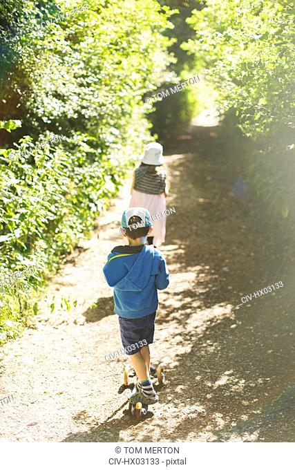 Boy and girl walking on sunny tree lined park path