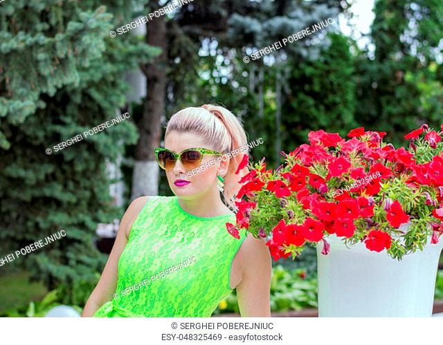 woman in sunglasses and beautiful Petunia, beautiful bright women summer theme and flowers