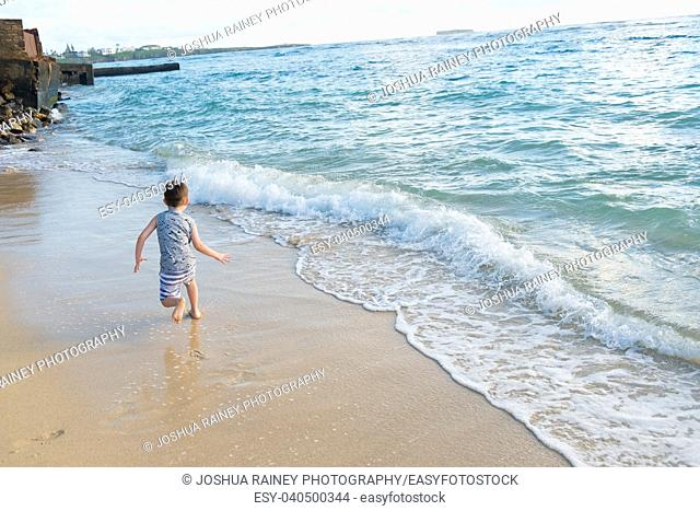 Five year old boy playing in the waves of the Pacific Ocean and having fun while on vacation in Oahu Hawaii