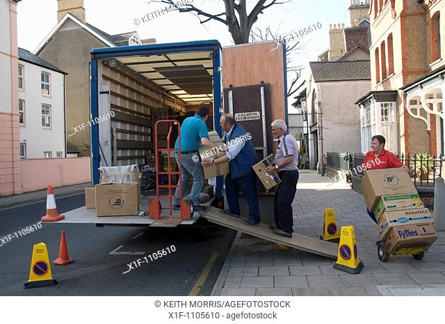 Moving House - Four men loading a removals lorry with cardboard boxes , Aberystwyth Wales UK