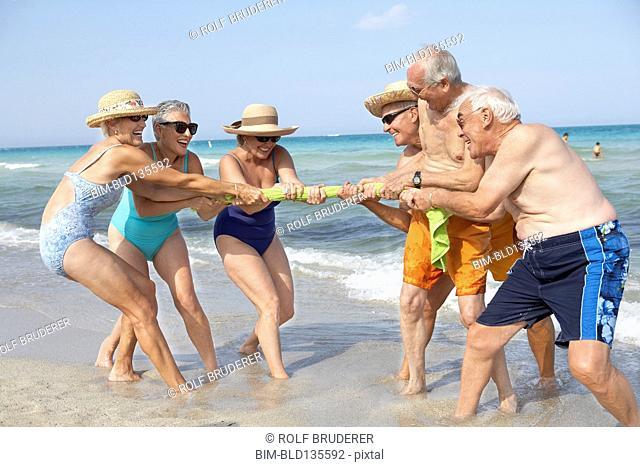 Senior friends playing tug-of-war on beach
