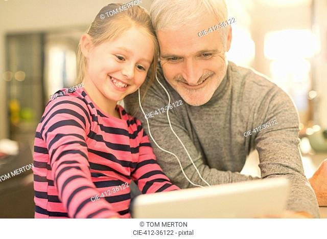 Smiling father and daughter sharing headphones, watching video on digital tablet