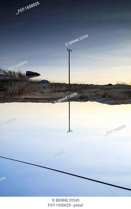 Electricity pylon reflecting in calm lake against blue sky