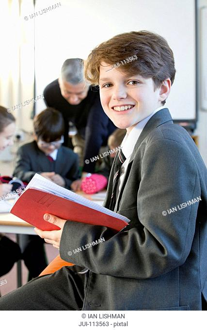 Portrait smiling middle school student with notebook in classroom