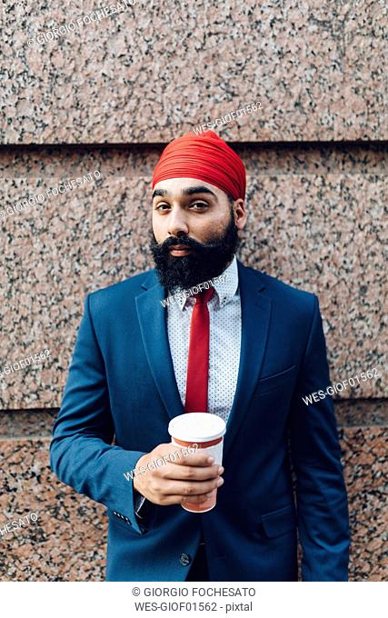 Indian businessman in Manhattan leaning against wall, drinking coffee