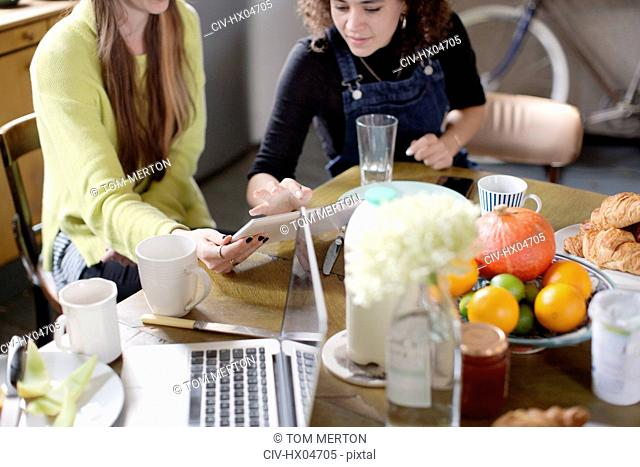Young women roommate friends using digital tablet at breakfast table
