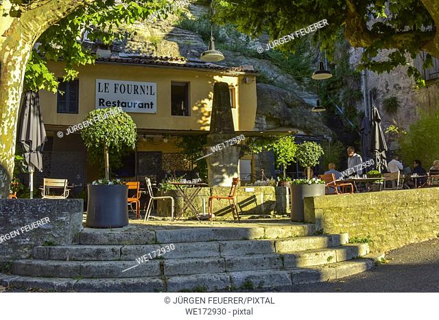 shady restaurant with Provencal atmosphere in Bonnieux, Provence, France, massif of Luberon, place on rock wall with well and plane trees
