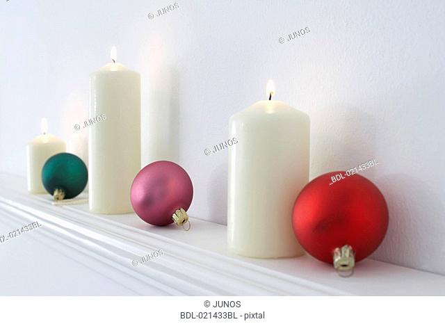 still life of burning candles and baubles