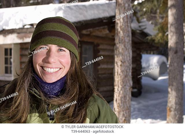 25-35 year old woman portrait in snow with log cabin in background. Teslin River Yukon Territory Canada