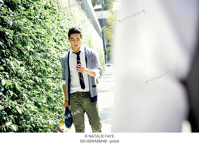Young man walking down street carrying skateboard and smartphone