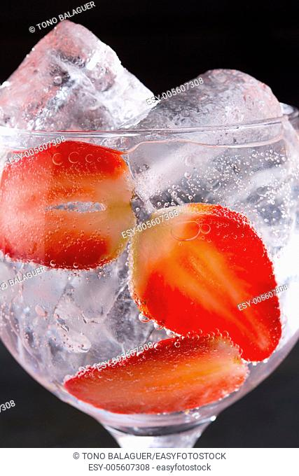 Gin tonic cocktail with strawberries ice macro closeup on black