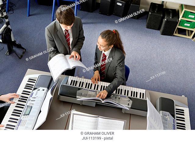 High school students reviewing sheet music at piano in music class