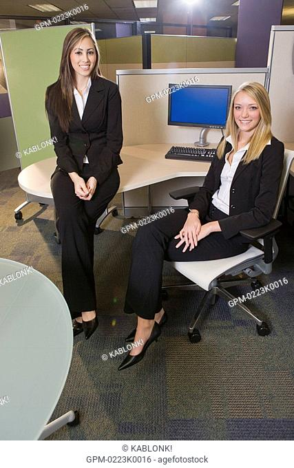 Portrait of young businesswoman sitting against table in office