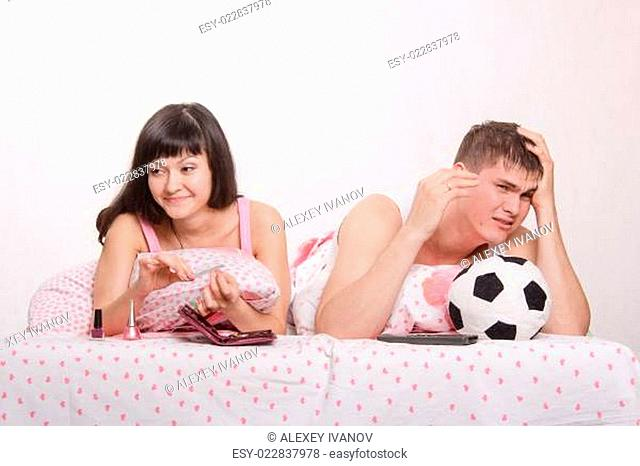 Husband not upset by a goal scored, skeptical wife smiling