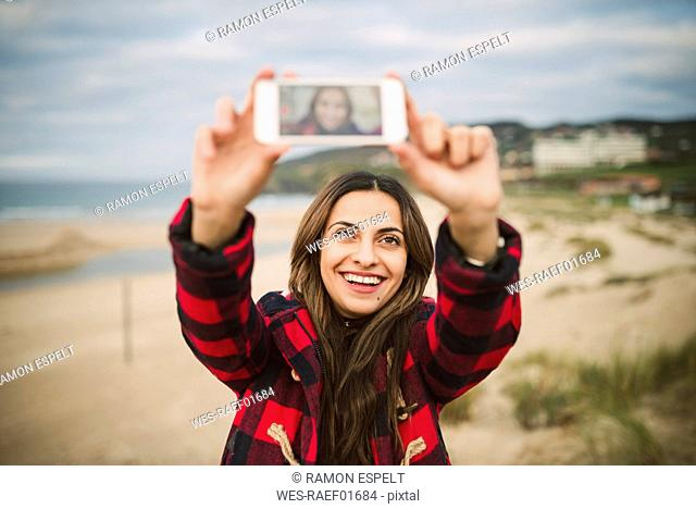 Portrait of smiling woman taking selfie with smartphone on the beach