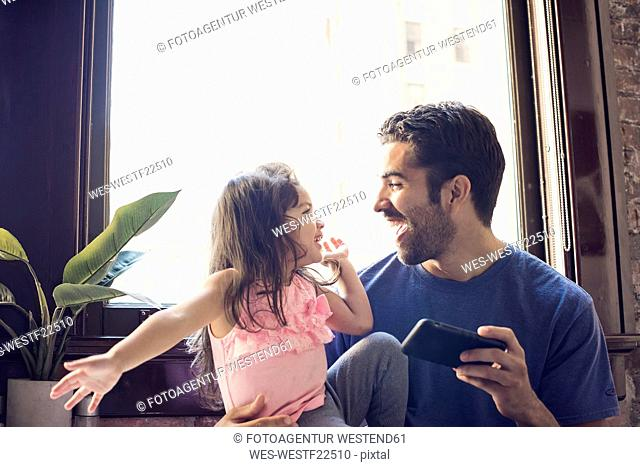 Father with daughter using smart phone in kitchen
