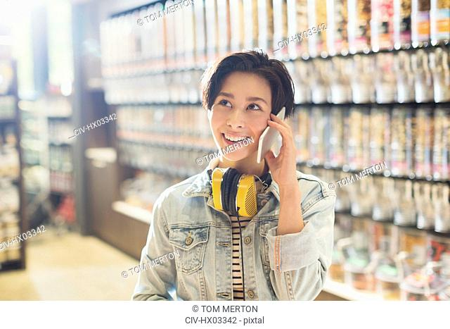 Smiling young woman with headphones talking on cell phone in grocery store market
