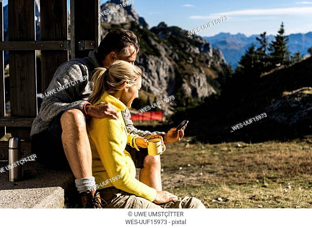 Hiking couple sitting in front of mountain hut, taking a break, looking at smartphone