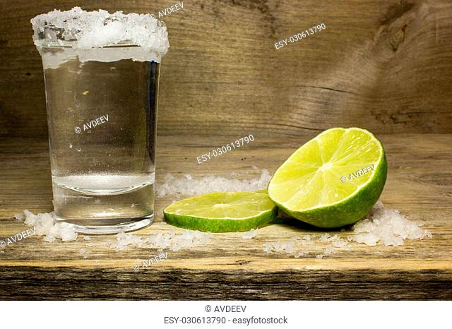 Tequila in a shot glass with lime wedges and salt