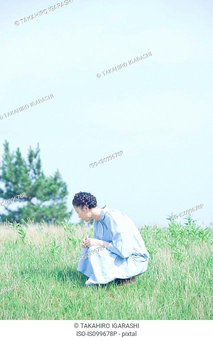 Young woman crouching in field