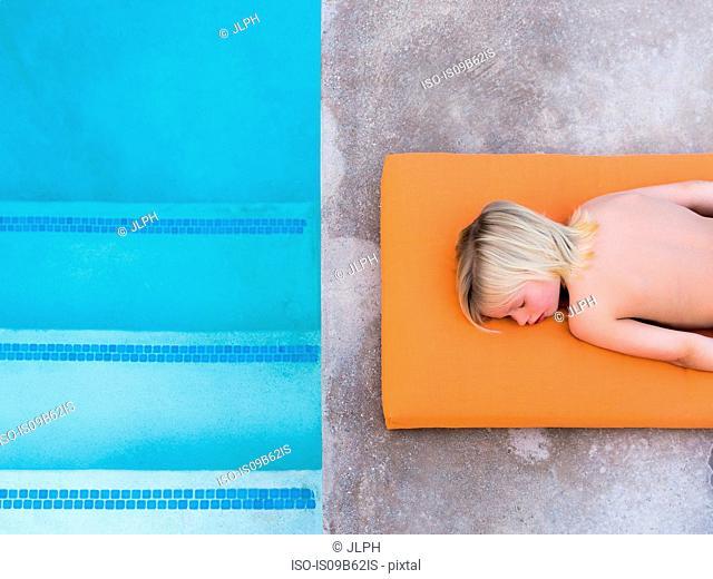 Overhead view of boy lying on poolside