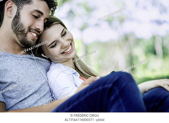 Young couple listening to music on smartphone
