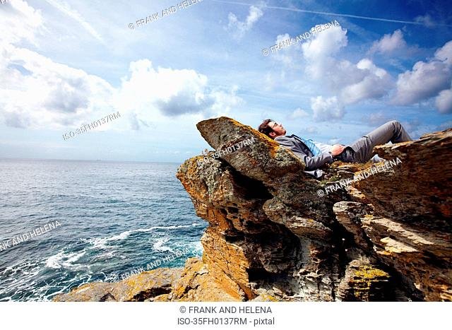 Businessman relaxing on cliff