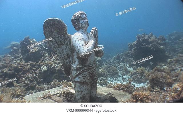 Cherub statue on coral reef, Reef check, Palawan, Philippines