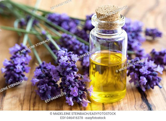 A bottle of essential oil with fresh lavender twigs on a wooden background