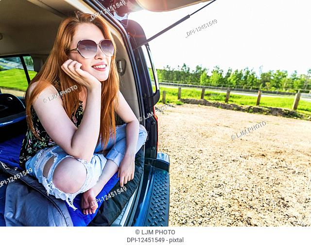 A young woman on a road trip lays in the back of a vehicle with her cell phone on a sleeping bag looking out from the open door; Edmonton, Alberta, Canada