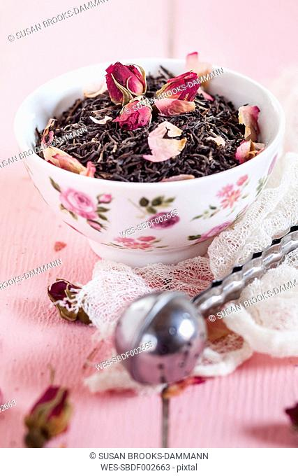 Bowl of black tea with dried rose blossoms