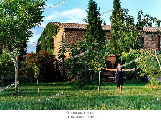Boy playing in garden of farmhouse