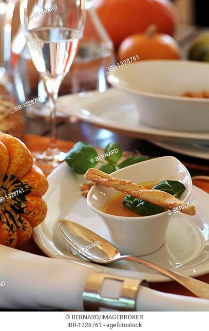 Cream of pumpkin soup served in fine porcelain on a table with autumn decorations