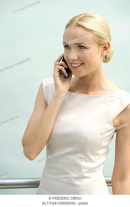 Young businesswoman talking on cell phone, smiling