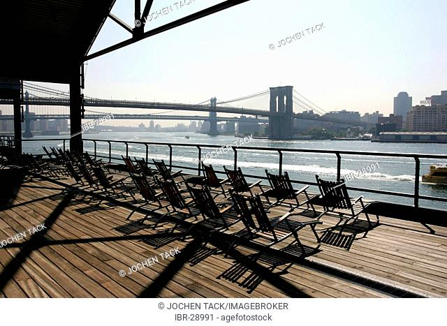 USA, United States of America, New York City: Pier 17, South Street Seaport. Chairs on the observation Deck. East River