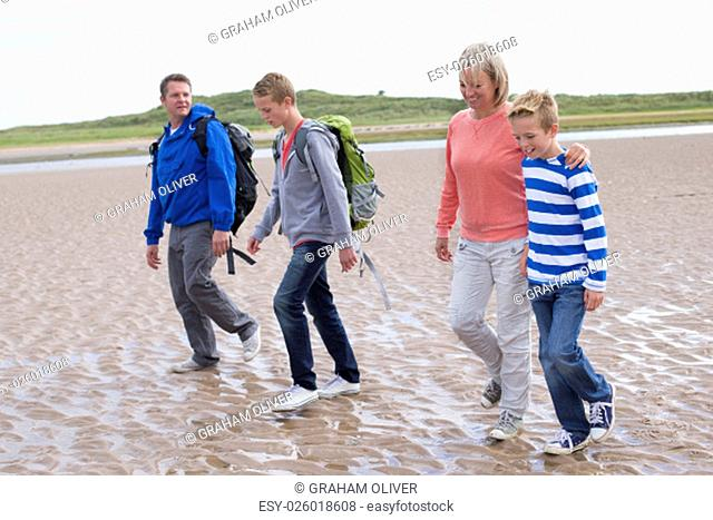 Family of four walking across the beach. They are wearing warm casual clothing with backpacks and look very happy