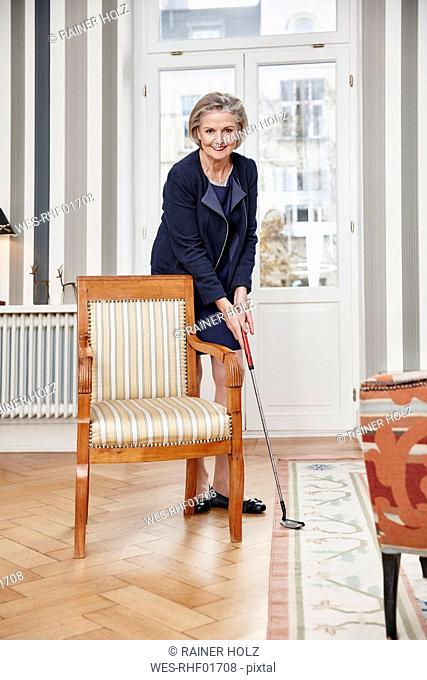 Senior woman playing golf at home
