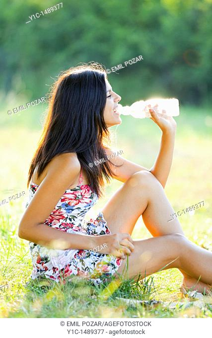 Attractive young woman on the grass, spilling water from a plastic bottle