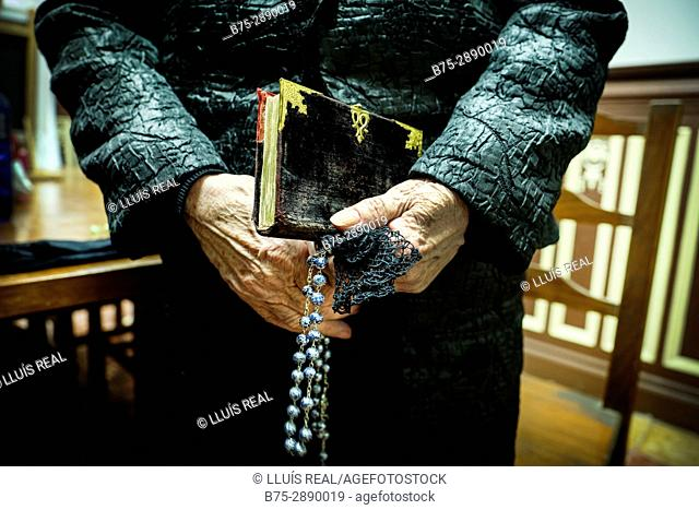 Close-up of the hands of a woman with a rosary and missal in Holy Week. Sant Josep church. Maho, Balearic Islands, Spain