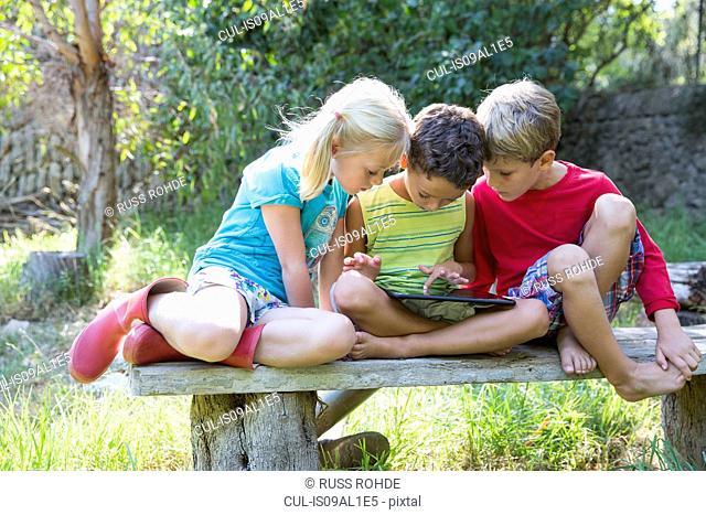 Three children sitting on garden seat looking down at digital tablet