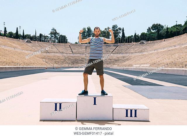 Greece, Athens, man on the podium celebrating in the Panathenaic Stadium