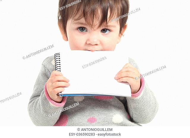 Baby biting a blank notebook on a white isolated background