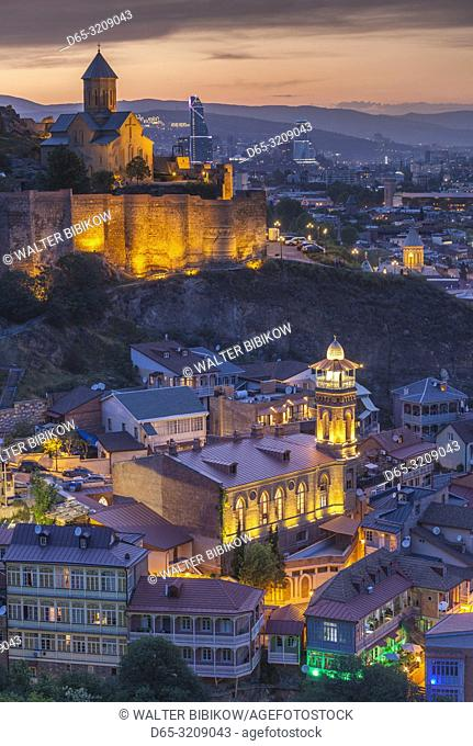 Georgia, Tbilisi, Old Town, Muslim Quarter and Narikala Fortress, high angle view, dusk