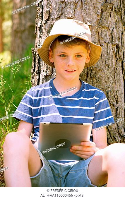 Boy using digital tablet in woods