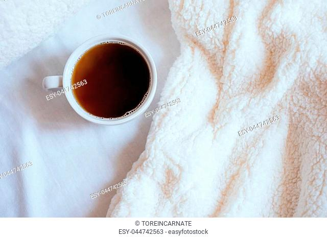 Big white morning cup of coffee in bed with pillow and cosy blanket