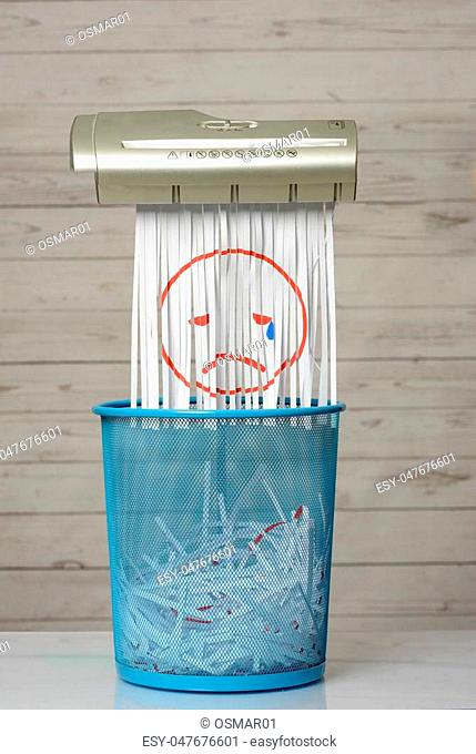 Destroy the sadness. Shredder documents with printed images concept thrown in the trash. White background and blue basket